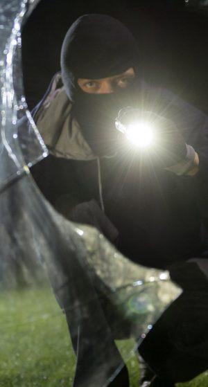 """ARCHIV- ILLUSTRATION - Ein fiktiver Einbrecher blickt am 23.07.2015 an einem Haus in Göppingen (Baden-Württemberg) durch eine eingeschlagene Fensterscheibe (gestellte Szene). Foto: Daniel Maurer/dpa (zu dpa: """"Plädoyers im Prozess gegen mutmaßliche Diebesbande aus Georgien"""" vom 15.04.2016) +++(c) dpa - Bildfunk+++"""
