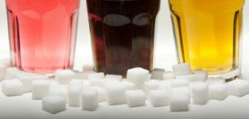 ARCHIV - ILLUSTRATION - Drei Gläser gefüllt mit roter Limonade, Cola und Energy-Drink stehen am 23.08.2016 in Berlin neben Zuckerwürfeln auf einem Tisch. Foto: Monika Skolimowska/dpa (zu dpa: «Umfrage: Deutsche skeptisch bei Zucker-Steuer» vom 12.09.2016) +++(c) dpa - Bildfunk+++